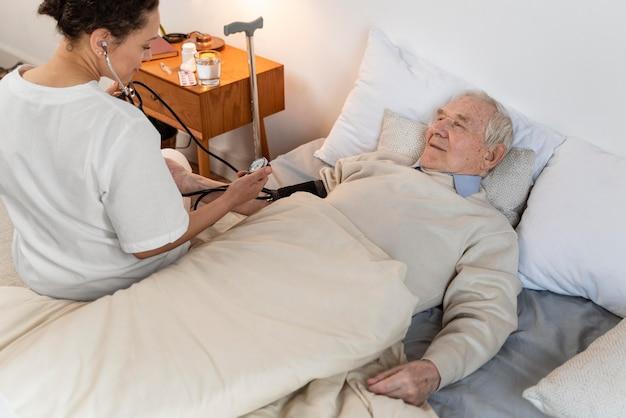 Arzt, der den blutdruck eines männlichen patienten überprüft
