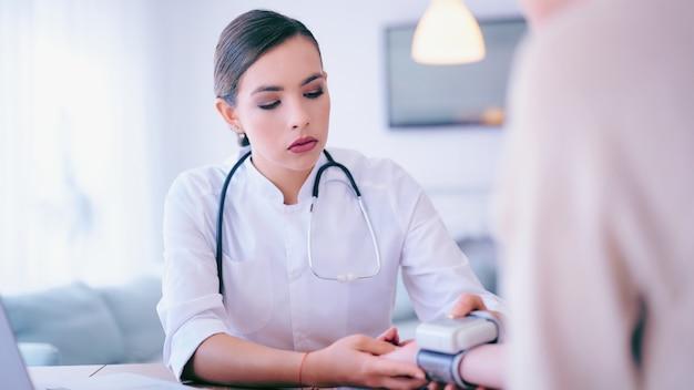 Arzt, der den blutdruck zum patienten im krankenhaus überprüft