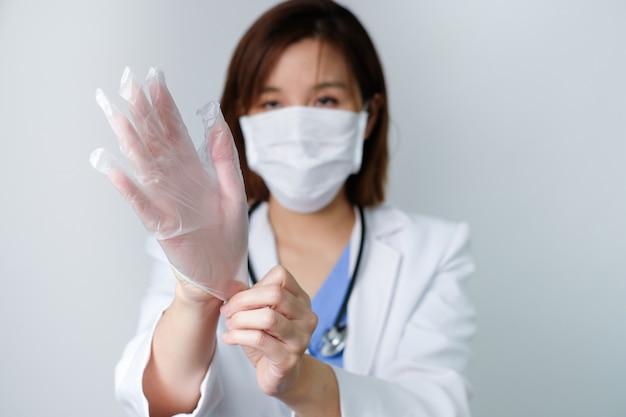 Arzt, der den handschuh trägt, um krankheit, infektion, covid19, koronavirus zu verhindern und zu bekämpfen.