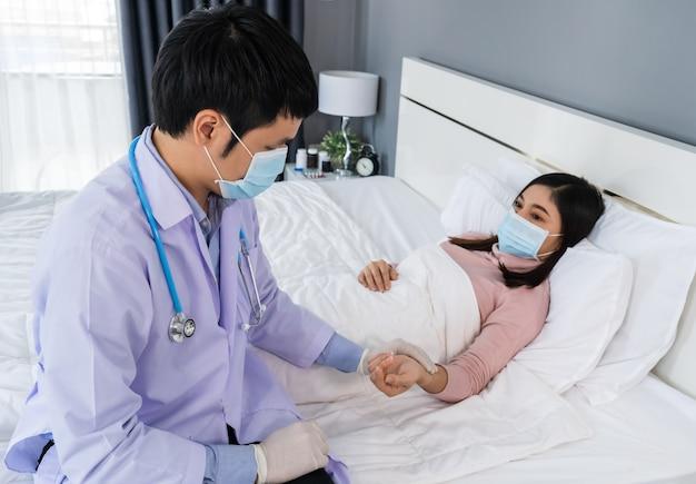 Arzt, der den patienten in einem krankenzimmer überprüft