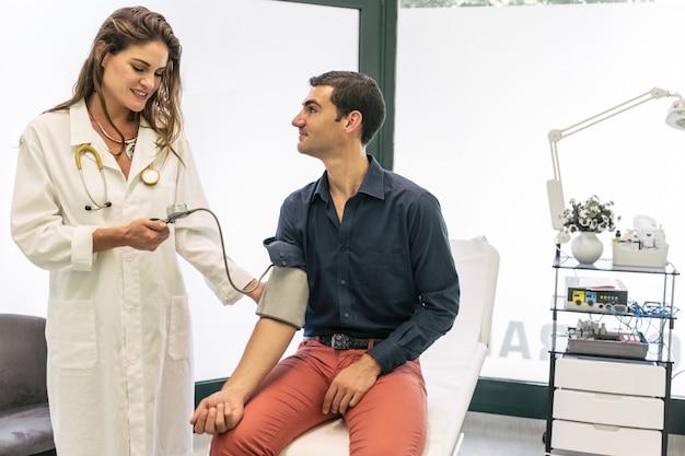 Arzt, der den patientendruck mit einem medizinischen werkzeug misst