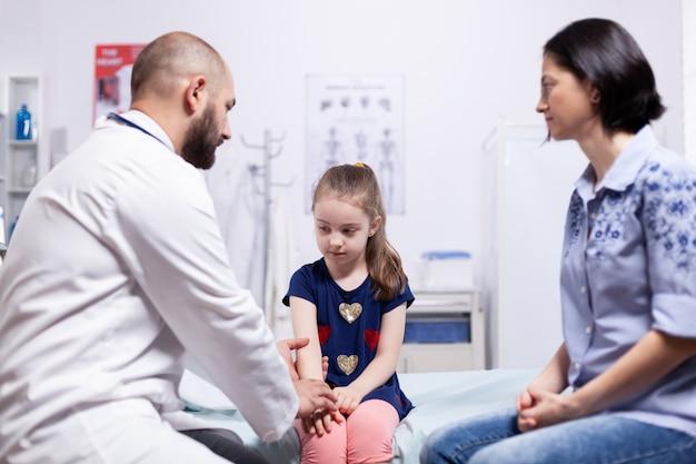 Arzt, der der mutter des kranken kindes im krankenhausbüro eine diagnose gibt. arzt im gesundheitswesen facharzt für medizin, der die behandlung von gesundheitsdienstleistungen anbietet.
