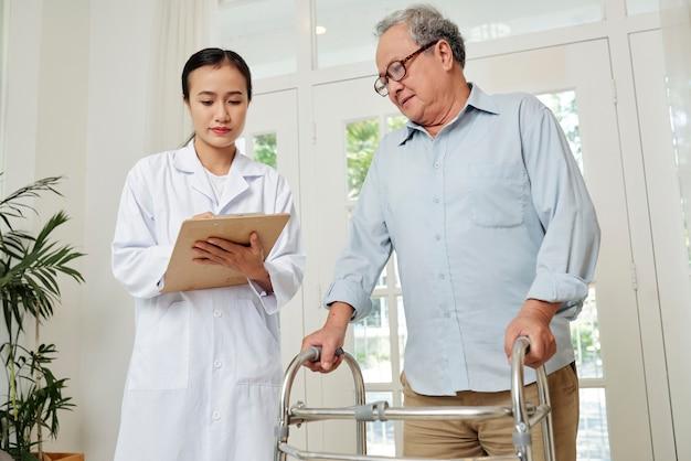 Arzt, der die gesundheit eines älteren patienten kontrolliert