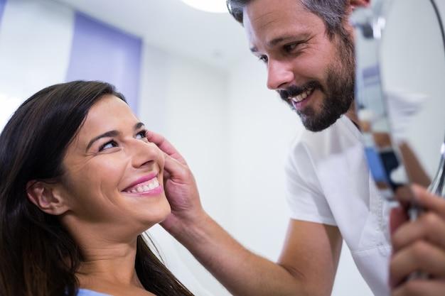 Arzt, der die haut des patienten nach einer kosmetischen behandlung überprüft