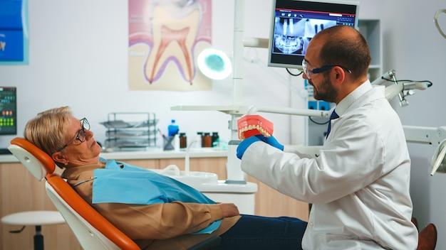 Arzt, der die richtige zahnhygiene anhand eines modells des zahnskeletts zeigt. zahnarzt, der einem alten patienten, der eine probe des menschlichen kiefers mit einer zahnbürste im stomatologiebüro hält, die richtige zahnhygiene erklärt.