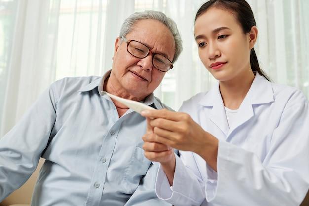 Arzt, der die temperatur des patienten kontrolliert
