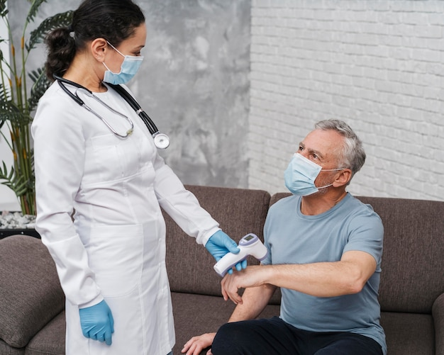 Arzt, der die temperatur des patienten misst