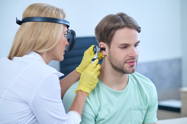 Arzt, der eine otoskopische untersuchung des gehörgangs des patienten durchführt