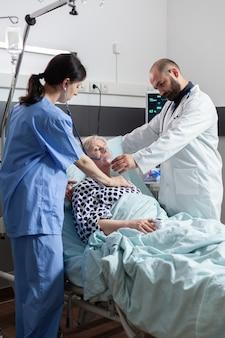 Arzt, der eine sauerstoffmaske für eine ältere patientin hält, die ihr beim atmen hilft