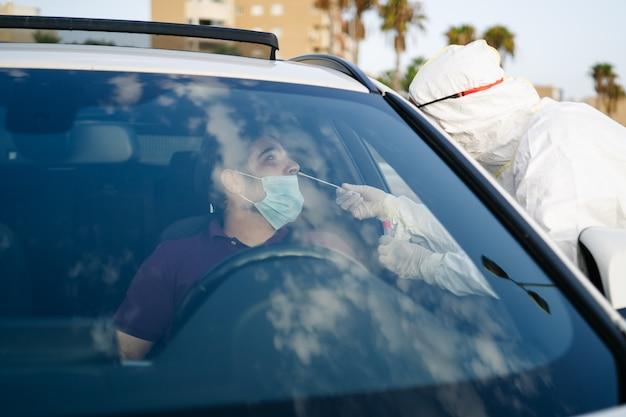Arzt, der einen pcr-test covid-19 an einem patienten durch das autofenster durchführt.