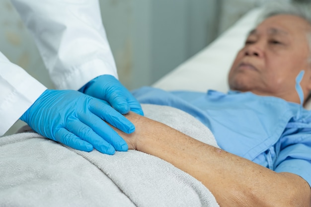 Arzt, der hände asiatische ältere frau patient mit liebe berührt.