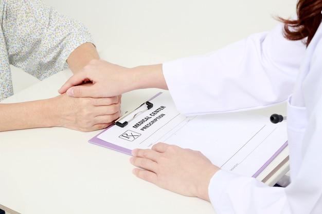 Arzt, der hände des patienten hält und tröstet