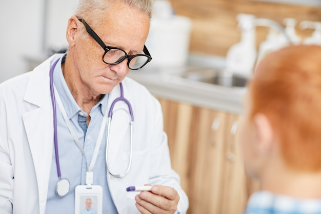 Arzt, der kinderfieber überprüft