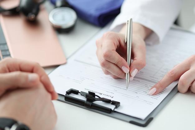 Arzt, der krankengeschichte des patienten in der nahaufnahme der klinik ausfüllt