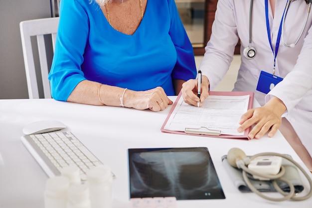 Arzt, der medizinisches dokument ausfüllt