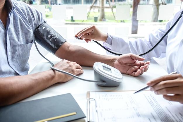 Arzt, der mit einem stethoskop die messung des arteriellen blutdrucks am arm eines patienten überprüft