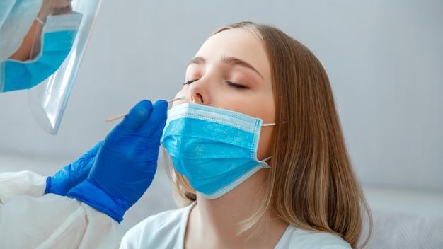 Arzt, der nasopharyngeale kultur, pcr-test an patientin nimmt. krankenschwester nimmt speichelprobe mit wattestäbchen durch die nase, um coronavirus covid 19 zu überprüfen. langes webbanner.