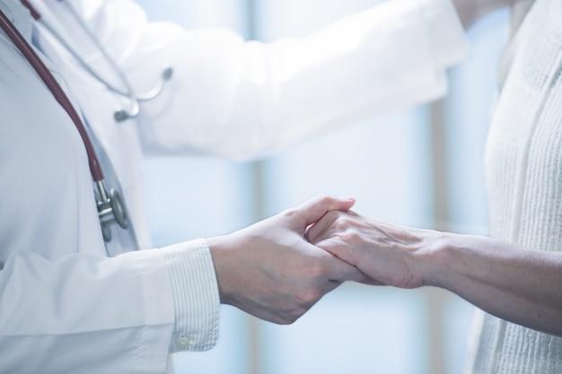 Arzt, der patienten durch händchenhalten in der krankenhauseinstellung beruhigt