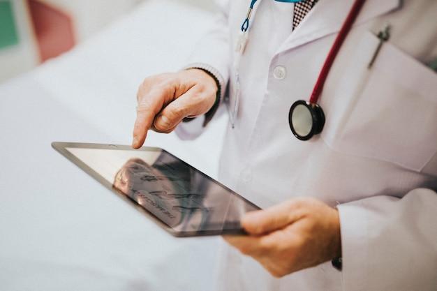 Arzt, der seine tablette betrachtet