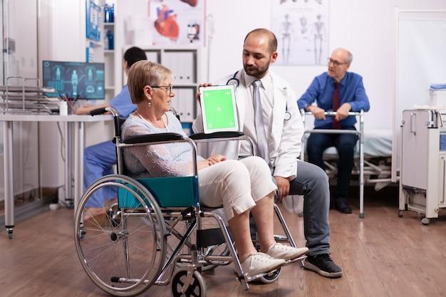 Arzt, der tablet-pc mit grünem bildschirm verwendet, während er eine behinderte ältere frau im rollstuhl konsultiert