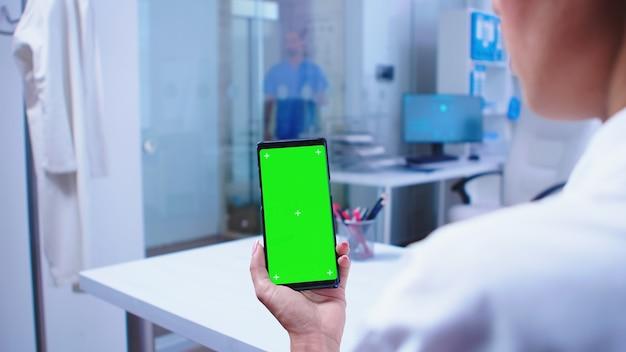 Arzt, der telefon mit grünem bildschirm im krankenhausschrank ansieht und krankenschwester aus dem aufzug steigt. gesundheitsspezialist im krankenhausschrank mit smartphone mit modell.