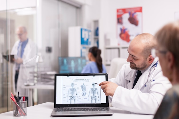 Arzt, der während der konsultation der alten frau vor der operation auf dem laptop im krankenhausbüro auf das menschliche skelett zeigt. senior sanitäter mit weißem kittel, der notizen über die zwischenablage im klinikflur macht.