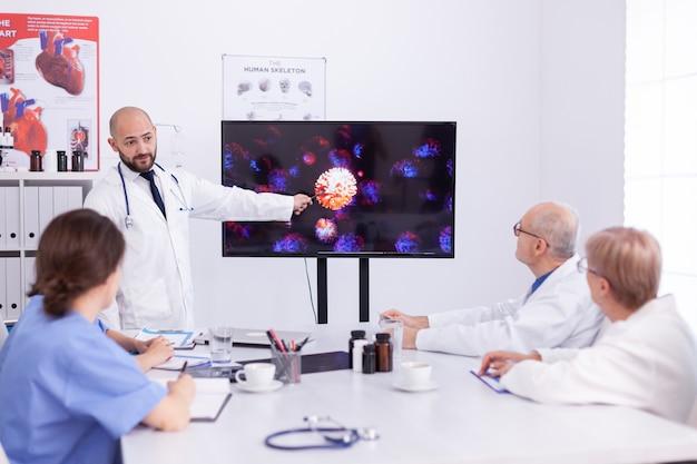 Arzt, der während eines treffens mit medizinischem personal eine präsentation über coronavirus hält. fachtherapeut diskutiert mit kollegen über globale pandemie wegen gefährlicher viren, symptome.