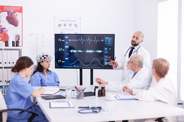 Arzt diskutiert über die zukunft der neurologie mit medizinischem personal im besprechungsraum des krankenhauses. der monitor zeigt eine moderne gehirnstudie, während das wissenschaftlerteam das gerät anpasst.