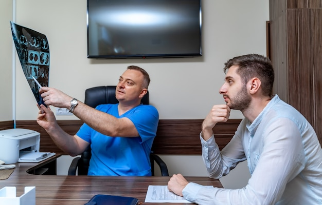 Arzt erklärt dem patienten in der arztpraxis ein röntgenbild. männlicher patient in der arztpraxis.