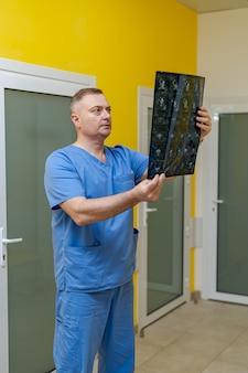 Arzt erklärt ein röntgenbild in der nähe des maschinenraums für magnetresonanztomographie.