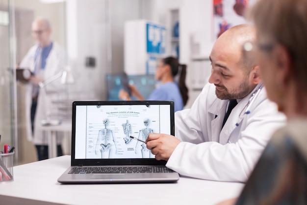 Arzt erklärt einem älteren patienten im krankenhausbüro rückenschmerzen und zeigt auf den laptop-bildschirm mit menschlichem skelett. krankenschwester in blauer uniform, die röntgenaufnahmen hält, und älterer arzt, der notizen über die zwischenablage macht