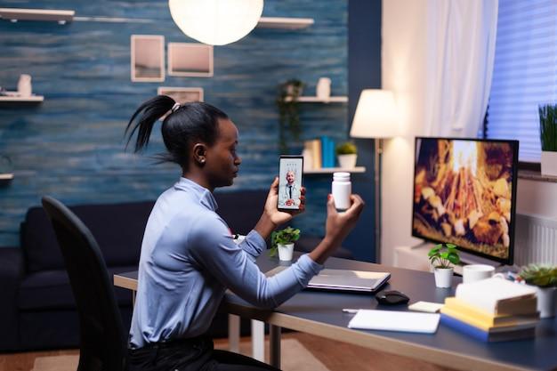 Arzt erklärt einer dunkelhäutigen frau während eines videoanrufs spät in der nacht die behandlung, während sie eine pillenflasche hält. schwarzer patient in einem videoanruf mit einem mediziner, der gesundheitliche probleme der frau bespricht.