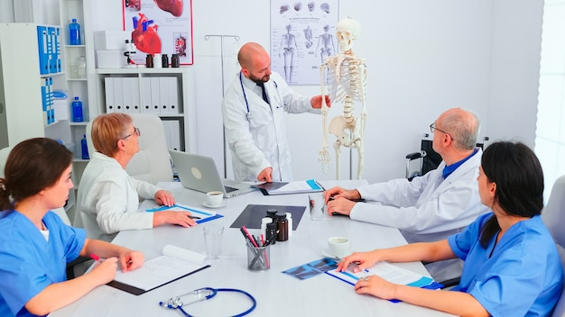 Arzt erklärt radiographie vor medizinischem personal im krankenhaus-konferenzraum unter verwendung des menschlichen skelettmodells. klinik-expertentherapeut im gespräch mit kollegen über krankheit, mediziner