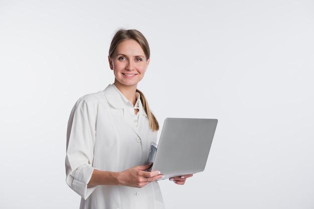 Arzt frau lächeln halten tablet pc, mit computer. krankenschwester über weißem hintergrund isoliert