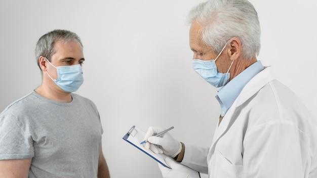 Arzt füllt informationen auf notizblock vor der impfung eines männlichen patienten aus