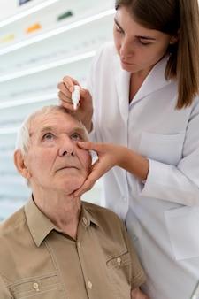 Arzt gießt einem patienten augentropfen ein