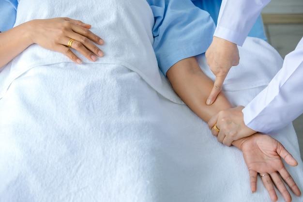 Arzt hält die hand des patienten auf dem bett im krankenhaus und überprüft das nervensystem zur heilung und behandlung. konzept des guillain-barre-syndroms und der tauben handkrankheit oder der impfstoffnebenwirkung.