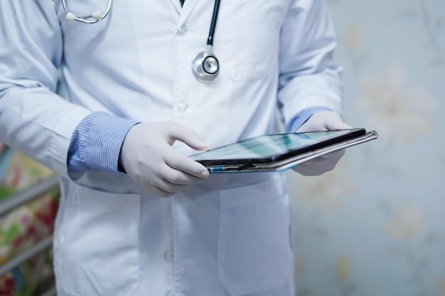 Arzt hält digitales tablett, um daten für behandelnden patienten im krankenhaus zu suchen
