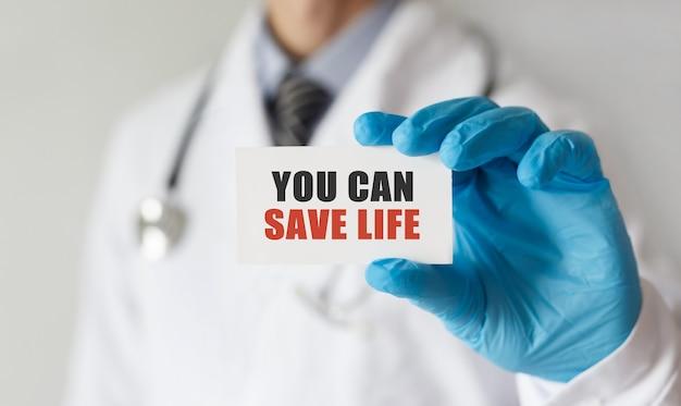Arzt hält eine karte mit text sie können leben retten, medizinisches konzept