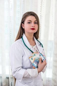 Arzt hält euro-banknoten, medizin und bestechung