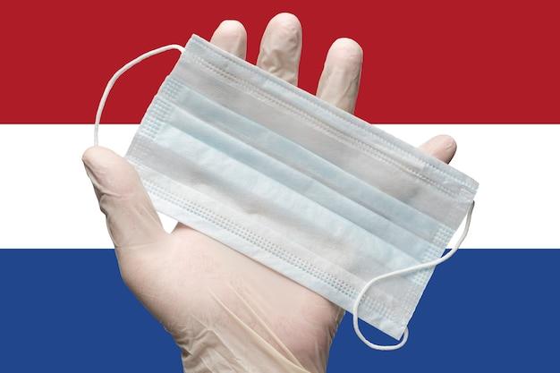 Arzt hält gesichtsmaske in der hand im weißen medizinischen handschuh auf der hintergrundflagge des niederländischen konzepts