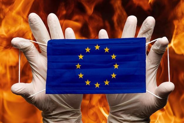 Arzt hält in weißen handschuhen medizinische gesichtsmaske, atembandage mit eu-flagge der europäischen union über der maske. konzeptpandemieausbruch auf dem hintergrund des gefährlichen feuers der roten flammen