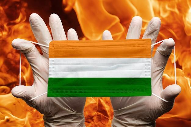 Arzt hält in weißen handschuhen medizinische gesichtsmaske atembandage mit indischer flagge