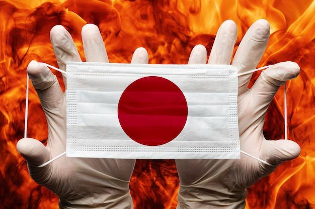Arzt hält in weißen handschuhen medizinische gesichtsmaske, atembandage mit japanischer nationalflagge auf maske. konzept auf dem hintergrund des natürlichen feuers der gefährlichen roten flammen