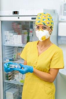 Arzt hält medizinimpfstoff. anti-virus-gesundheitsbehandlung. medizinische krankenschwester in maske. apotheke labor. forschungszentrum. sicherheitsverfahren. kühlschrank mit medizinhintergrund.