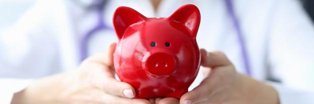 Arzt hält sparschwein in seinen händen krankenversicherungs- und zahlungskonzept