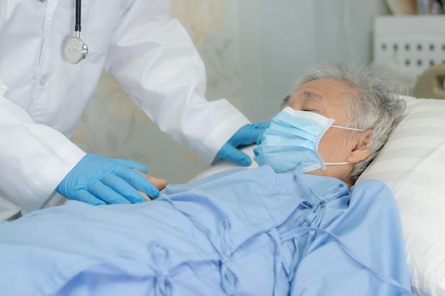 Arzt helfen asiatischen älteren fraupatienten, die eine gesichtsmaske im krankenhaus tragen.