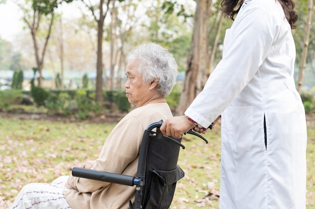 Arzt hilfe und pflege asiatische ältere patientin sitzt im rollstuhl im park