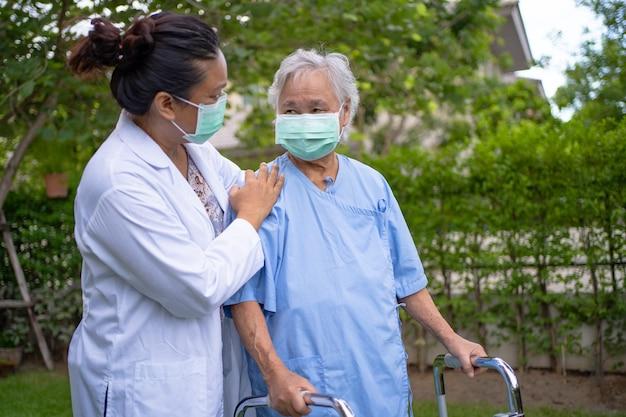 Arzt hilfe und pflege asiatische seniorin verwendet gehhilfe mit starker gesundheit beim gehen im park