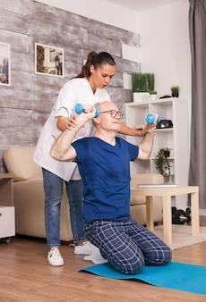 Arzt hilft älteren patienten, mit hanteln richtig zu trainieren.